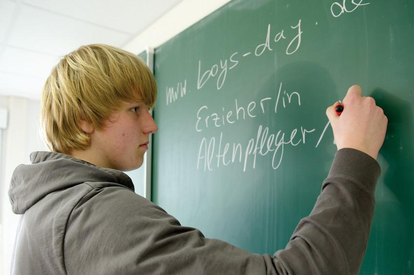 Schüler schreibt Berufe an die Tafel, in denen bisher nur wenige Männer arbeiten.